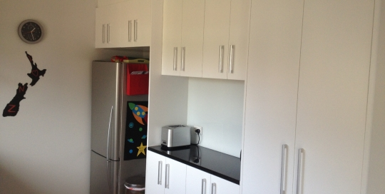 White doors with black top, full height pantry area