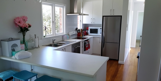 U shaped kitchen - white on white, timber floors